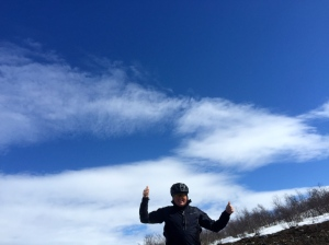 Double thumbs up under blue skies