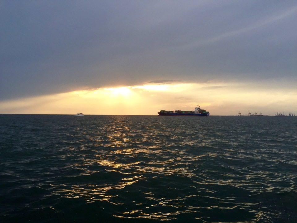Close to sunset; cargo ship moored in bay